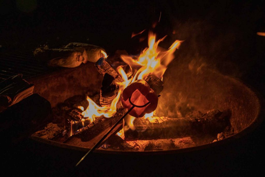 Someone roasts a pepper above a campfire.