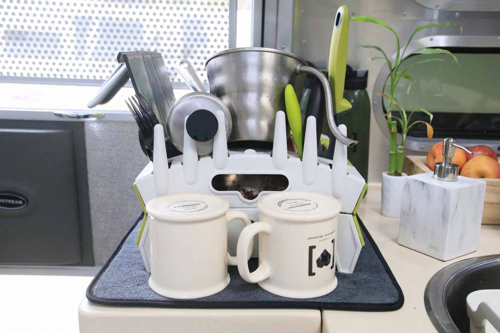 A collapsable drying rack with various plates and cups drying.