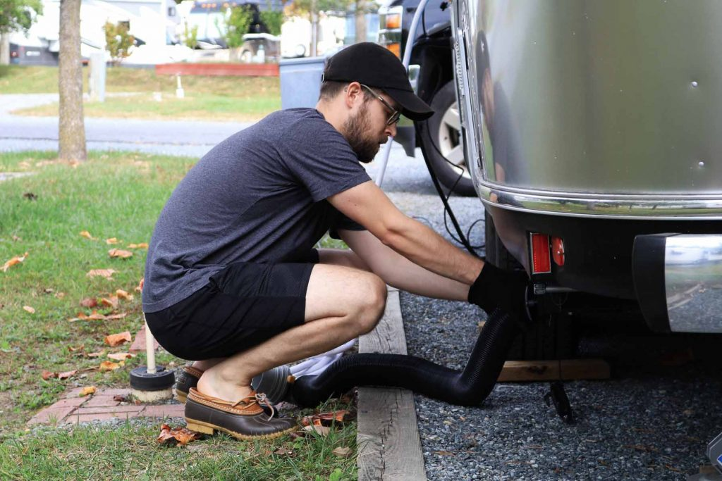 A man connects his sewage hose to his Airstream trailer.