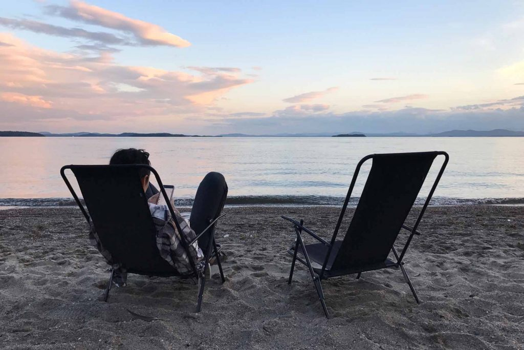 A woman sits on camp chairs looking out to Lake Champlain in Vermont.