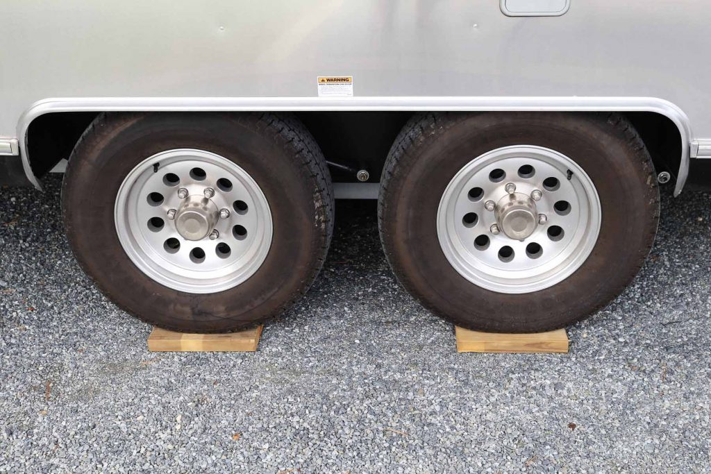 Tires of an RV on top of two wooden planks acting as levels.