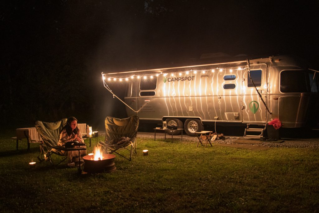 A woman sits by a campfire near an Airstream trailer at a campsite at the Finger Lakes Campground in Prattsburgh, New York.