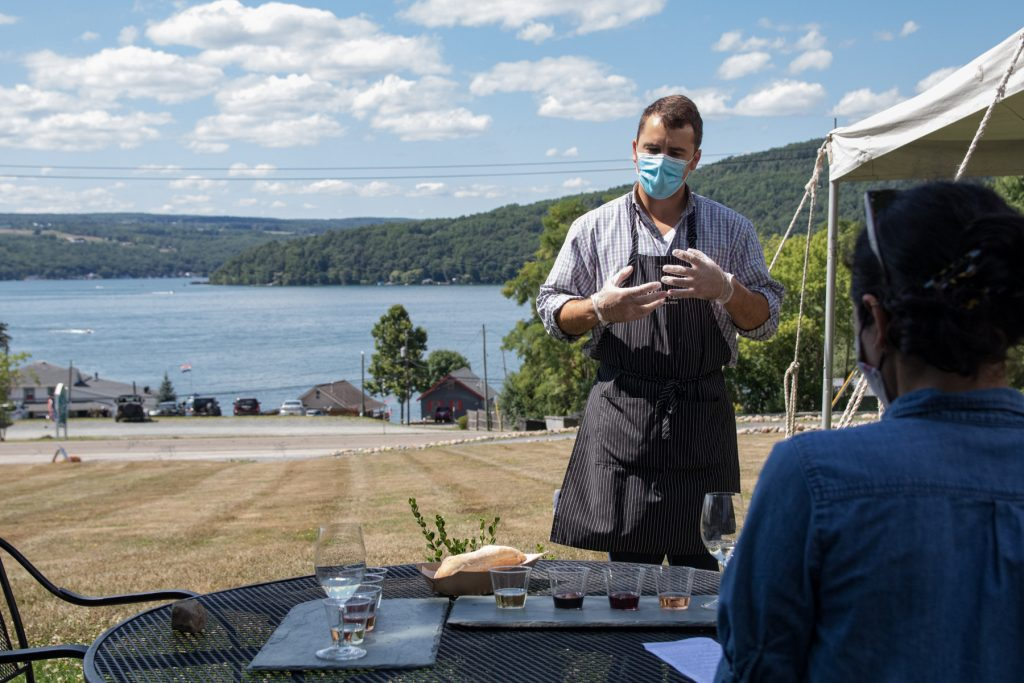 A man from Ravines Wine Cellars explains the tasting notes of a flight of wine with Lake Keuka behind him.