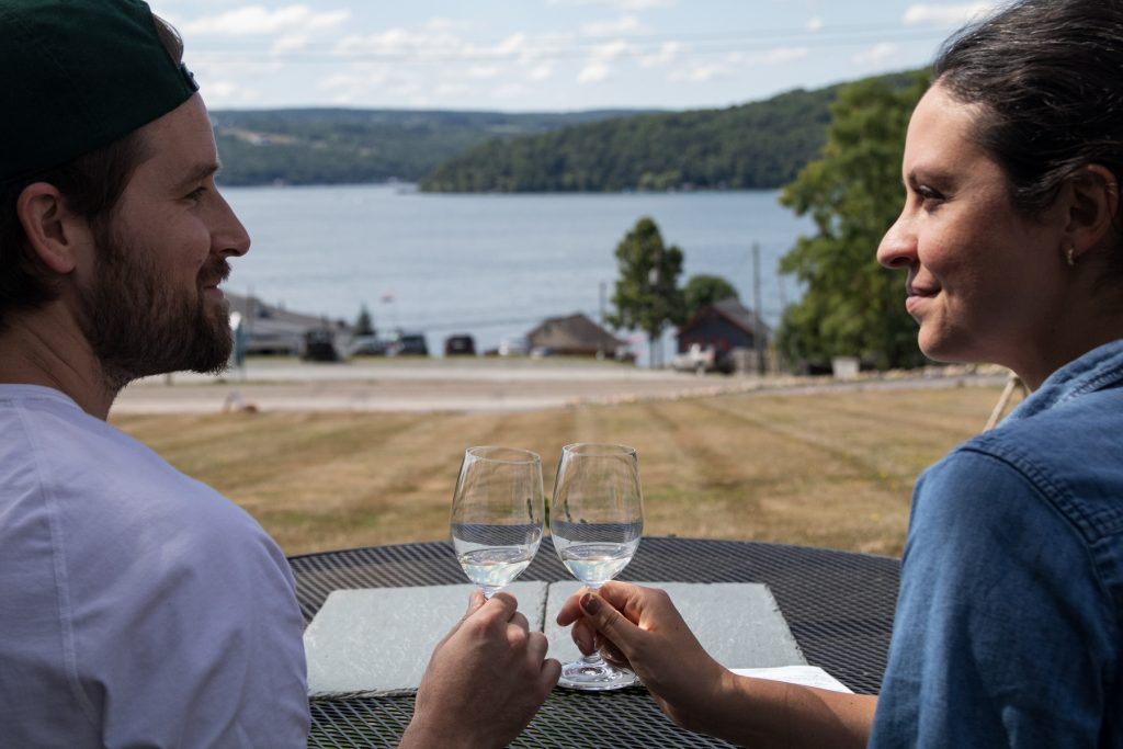 A man and a woman cheers at Ravines Wine Cellars on Keuka Lake in the Finger Lakes Region in upstate New York.