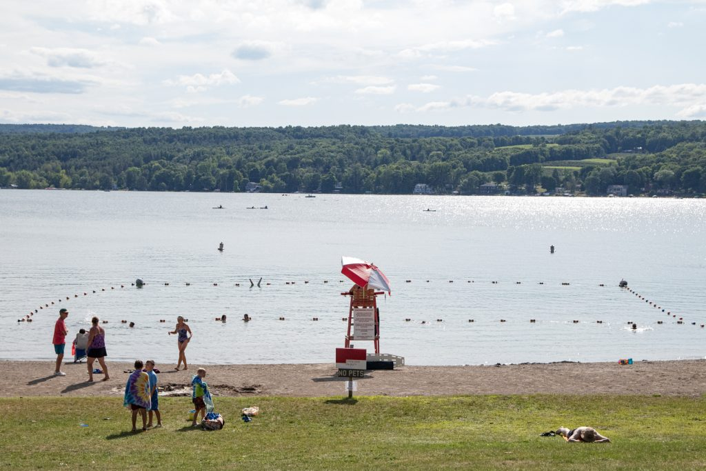 A lifeguard underneath an umbrella looking out to Keuka Lake with swimmers in the background.