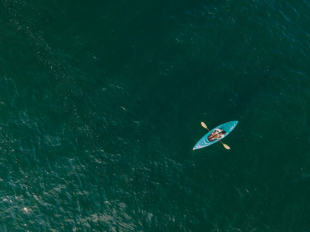 A birds-eye view of a woman kayaking Keuka Lake in the Finger Lakes Region of upstate New York.