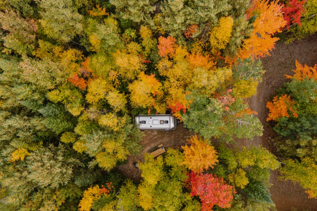 Airstream trailer in secluded fall foliage of Maine.
