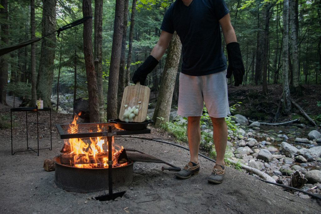 A man pours sliced onions into a Lodge cast iron pan sitting on top of a campfire grill with a roaring fire underneath.