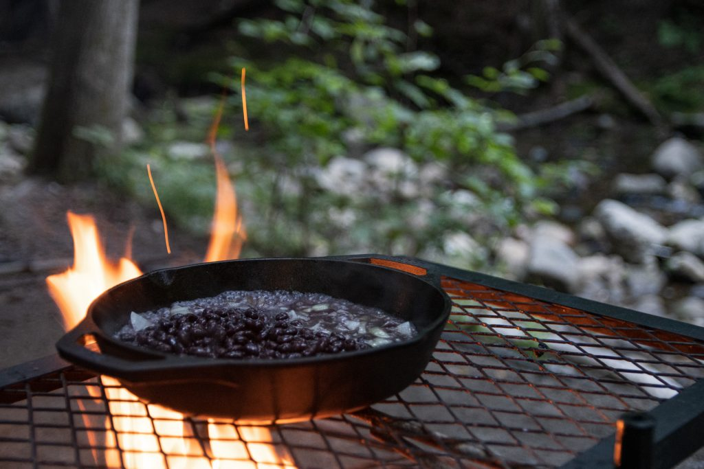 A Lodge cast iron pan full with black beans and onions sitting on top of a campfire grill with flames coming up from beneath.