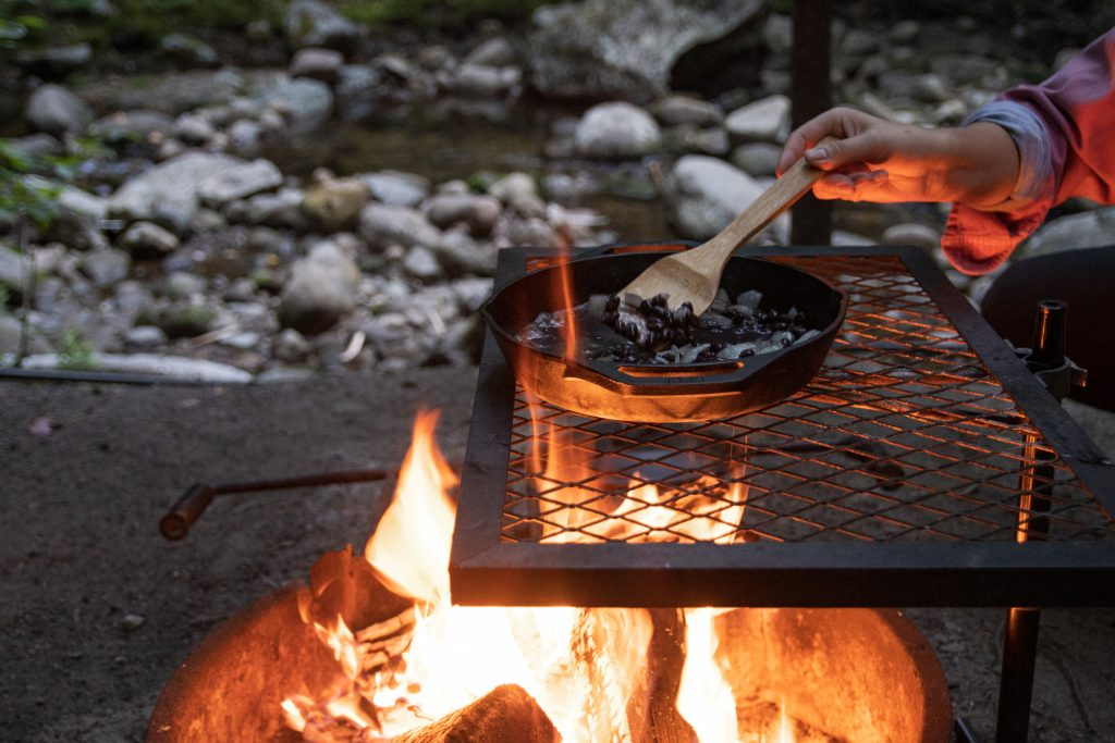 A person carefully stirs the Lodge cast iron pan of black beans with campfire flames coming up through the campfire grill.