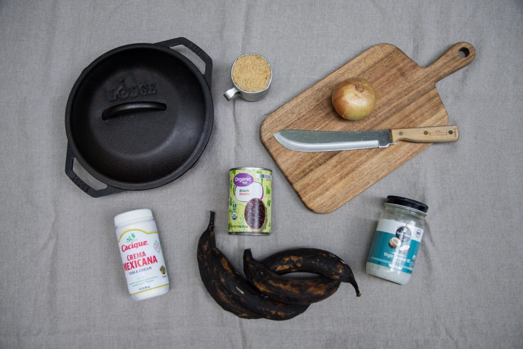 A top-down image of a Lodge cast iron pan, wooden cutting board, crema Mexicana, coconut oil, plantains, a can of black beans, onion, and cup of rice.