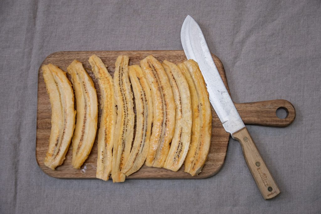 A top-down image of plantain halves sitting on top of a wooden cutting board with a knife next to them.