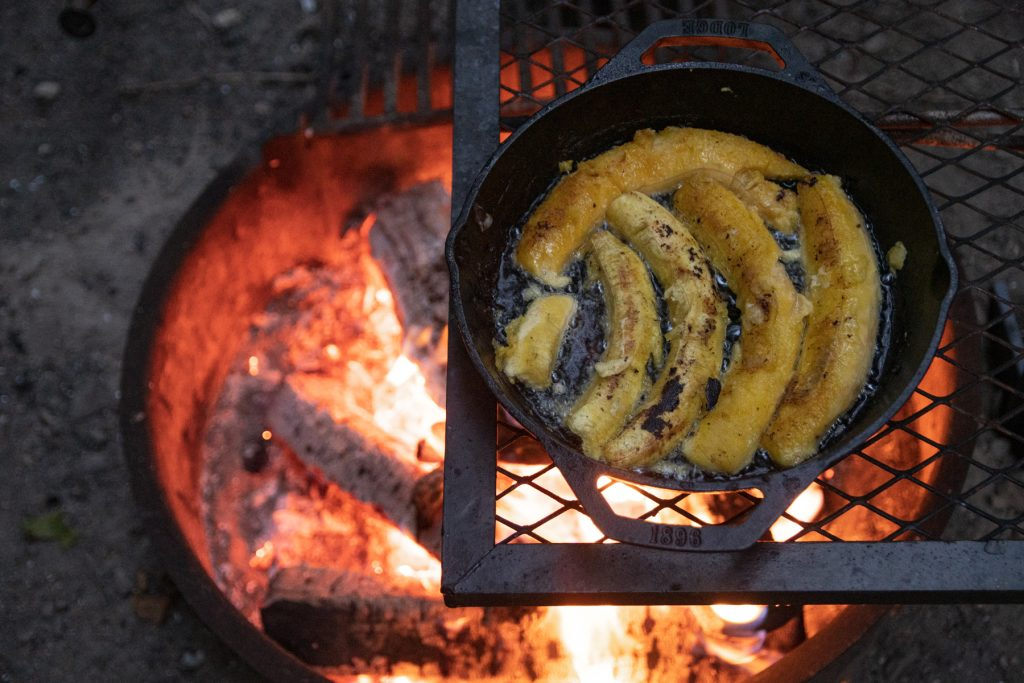 A top-down image of the plantain halves frying in coconut oil within the Lodge cast iron pan, sitting on top of the campfire grill grate and with glowing embers below.