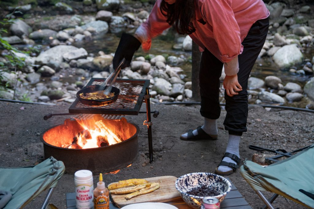 With a stoney creek behind, a woman carefully flips the frying plantains over with tongs.