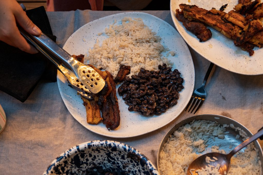 A person serves fried plantains onto a plate with black beans and rice.