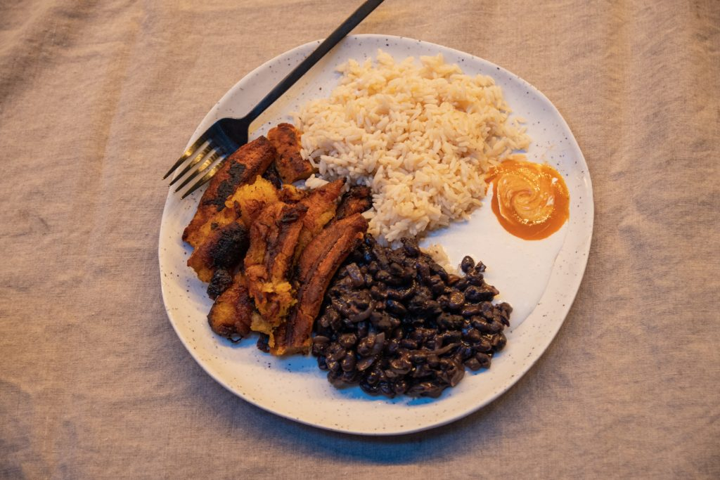 A top-down image of a plate full of fried plantains, rice, black beans, crema Mexicana, and hotsauce