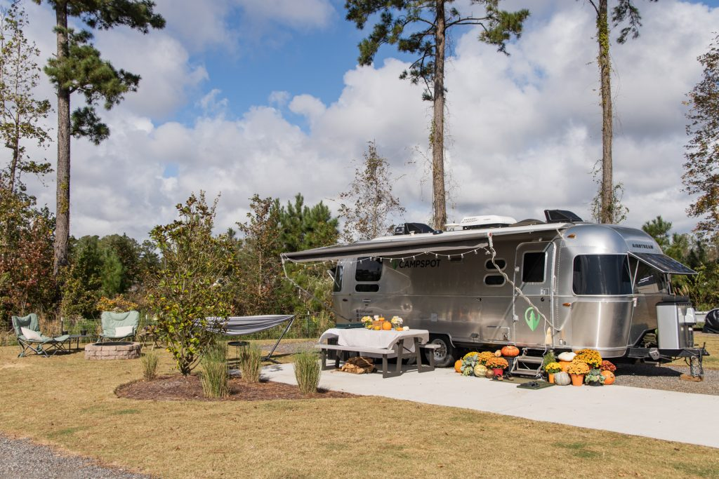 An example of an RV site with an Airstream surrounded by pine trees at Carolina Pines in Conway, South Carolina.