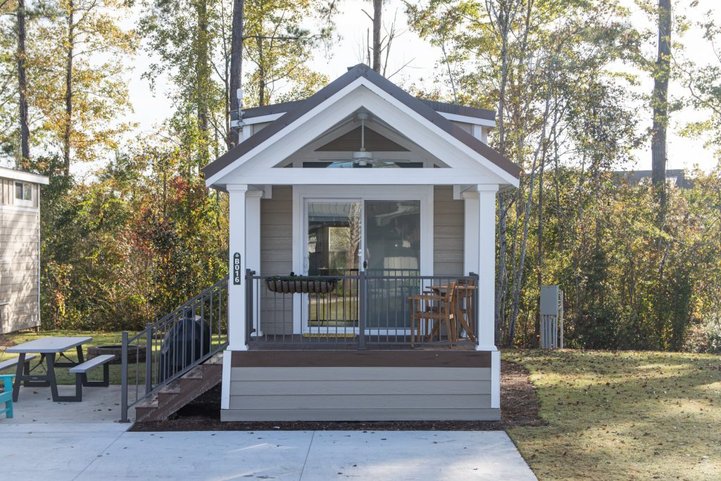 A Carolina cottage with a sliding door leading to the porch and a grill at Carolina Pines in Conway, South Carolina.