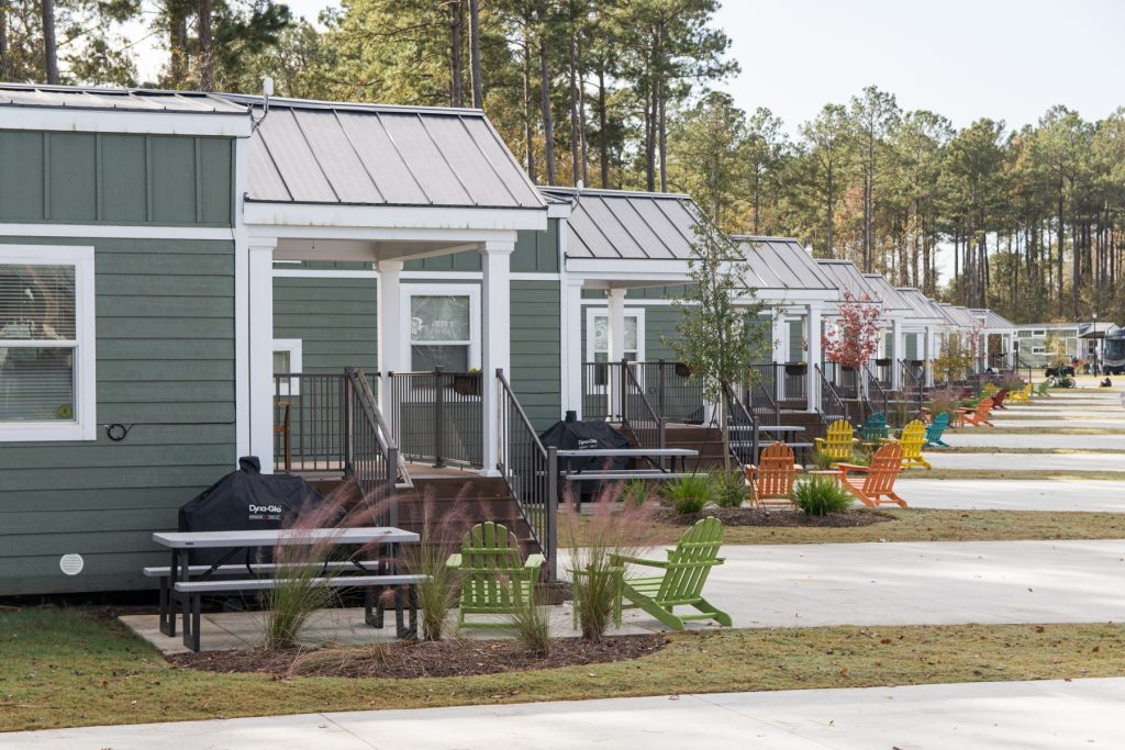 A row of green Carolina Cottages with a rainbow of Adirondack chairs at the Carolina Pines Resort in Conway, South Carolina.
