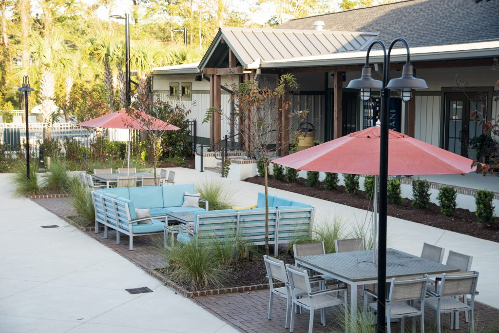 Outdoor seating areas, including a couch ad a large table with umbrella, in the Carolina Commons area at the Carolina Pines Resort in Conway, South Carolina.