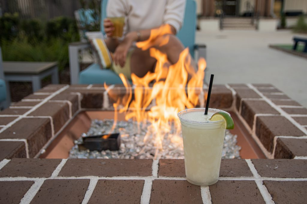 The outdoor fire pit with cocktails along the edge of it in the Carolina Commons area at Carolina Pines Resort in Conway, South Carolina.