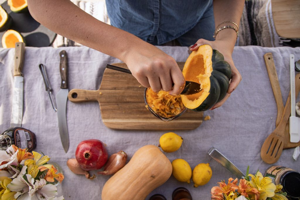 A person sits at a campground picnic table scooping out the insides of squash, preparing a meal for Thanksgiving.