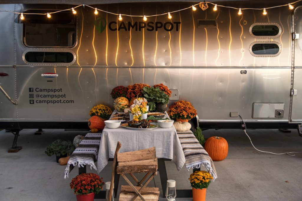 Underneath an Airstream awning with string lights, a picnic table is covered with a Thanksgiving spread.
