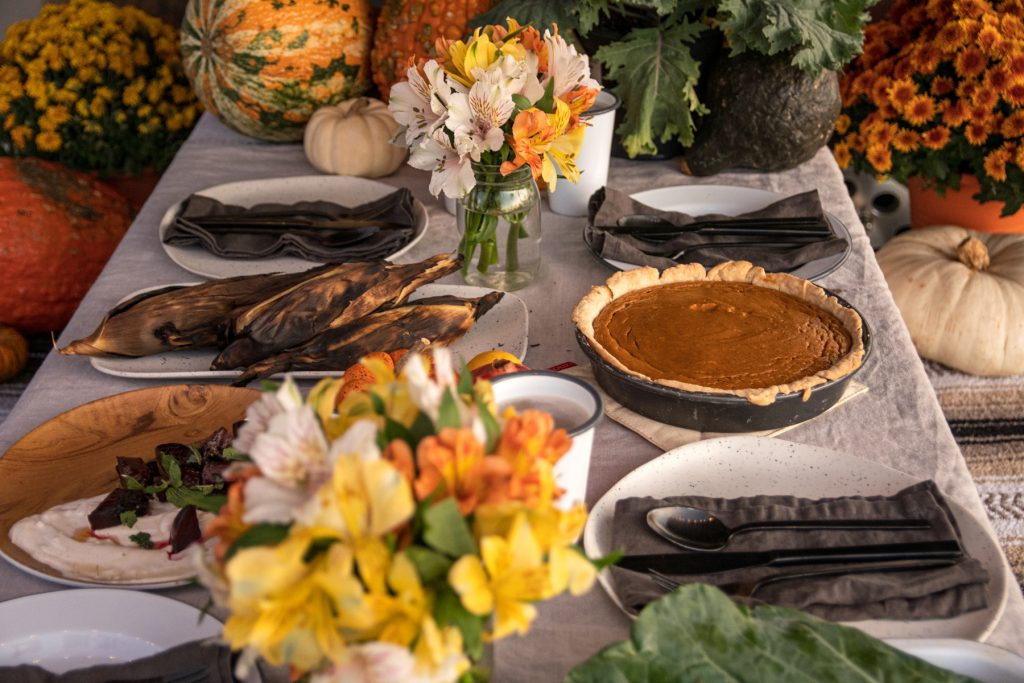 A platter of beets, campfire corn, and pumpkin pie sit on top of a campground picnic table covered with a tablecloth and decorative squash and flowers.