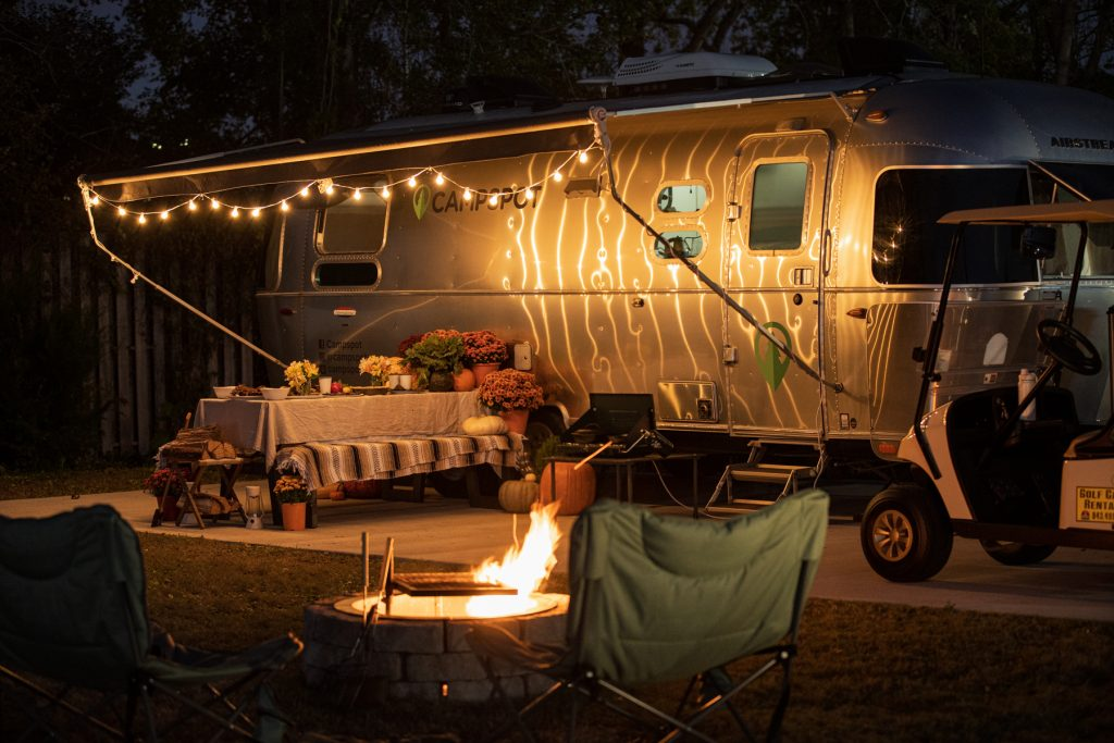A campfire is roaring as an Airstream trailer adorned with cafe lights sits int he background with a picnic table with a Thanksgiving meal sits below.