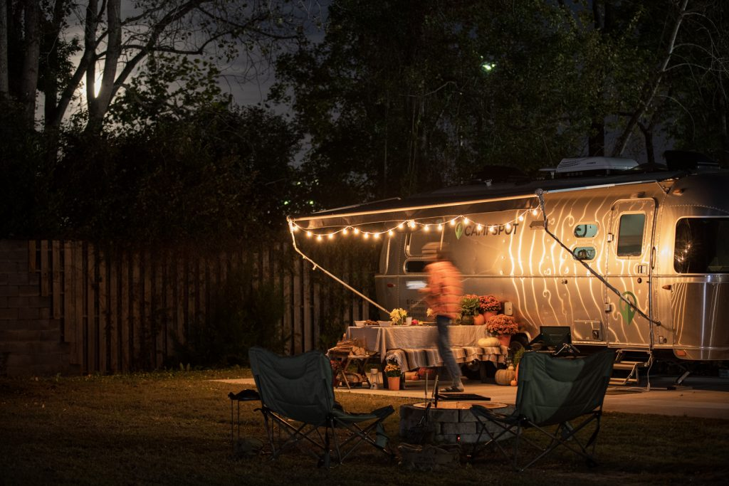 A person walks underneath an Airstream awning adorned with cafe lights at a campground.