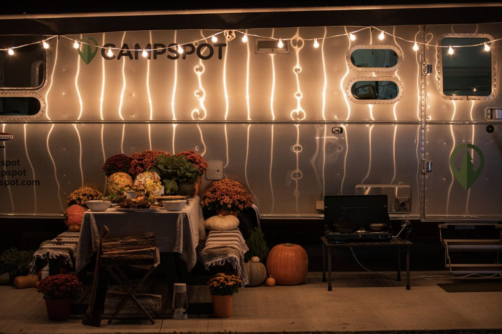A picnic table covered with mums, pumpkins, squash, and a Thanksgiving meal sits underneath an Airstream awning with glowing stringlights.