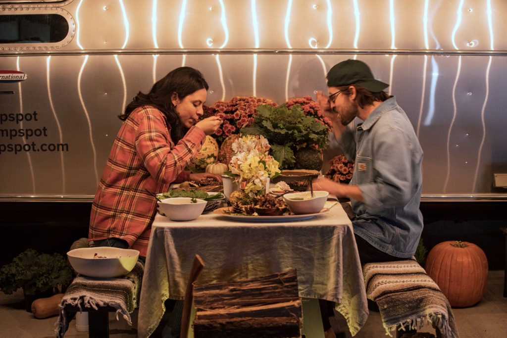 A couple enjoys a Thanksgiving meal sitting at a campground picnic table, surrounded by food and decorations.