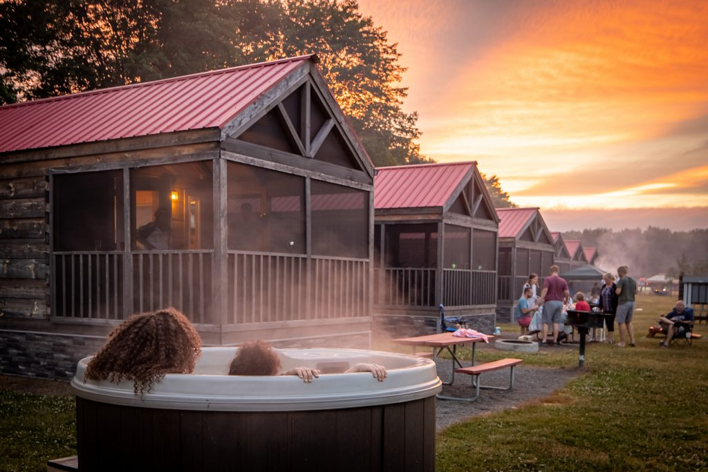 Mother and child in hot tub looking at the sunset outside of a camping cabin in Gardiner, New York Jellystone Park.
