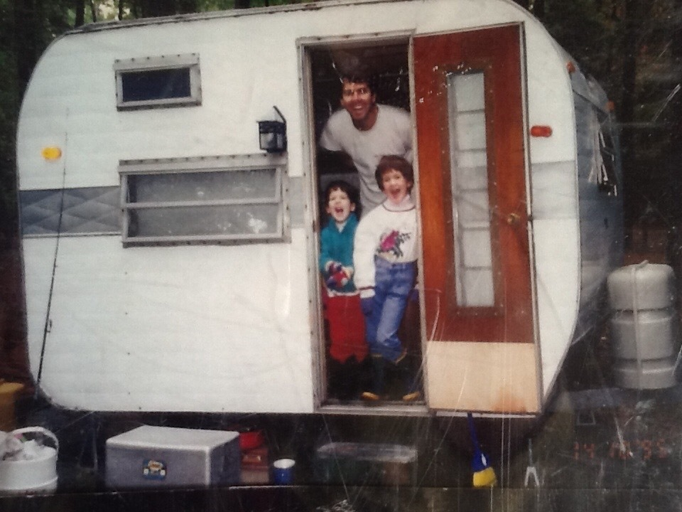 A man with two children in a vintage Shasta RV.