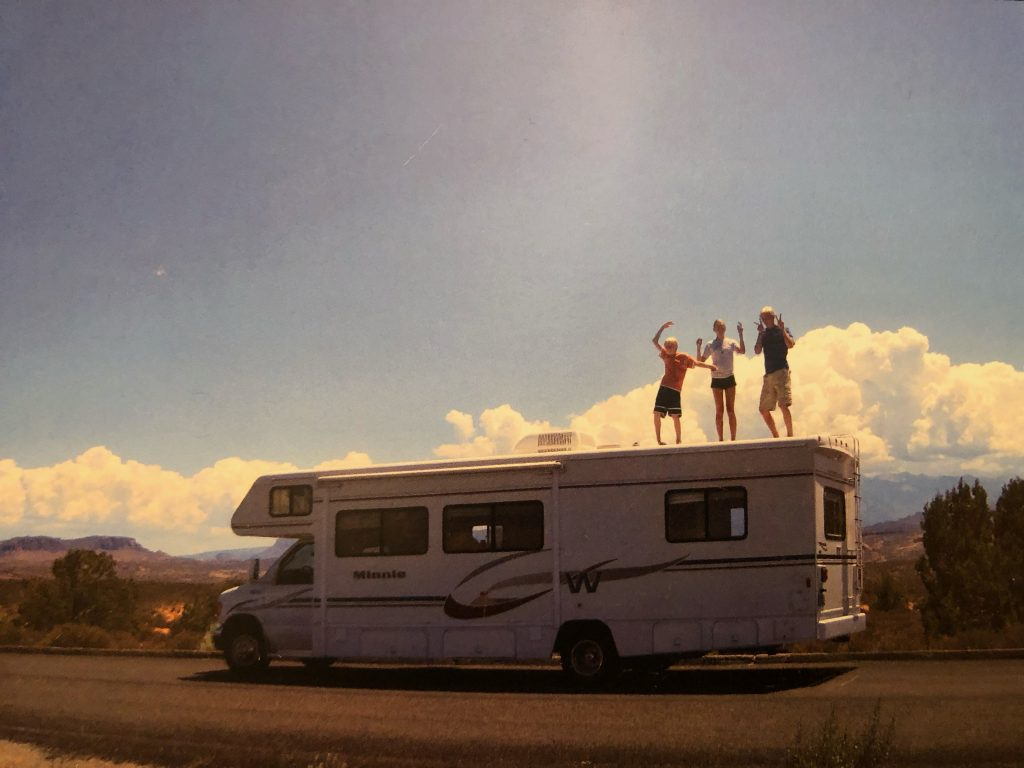 A vintage photo of three children dancing on top of an RV with mountains in the background.