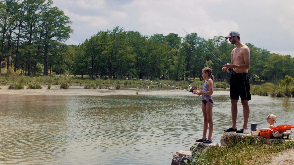 Father and daughter fishing while camping.