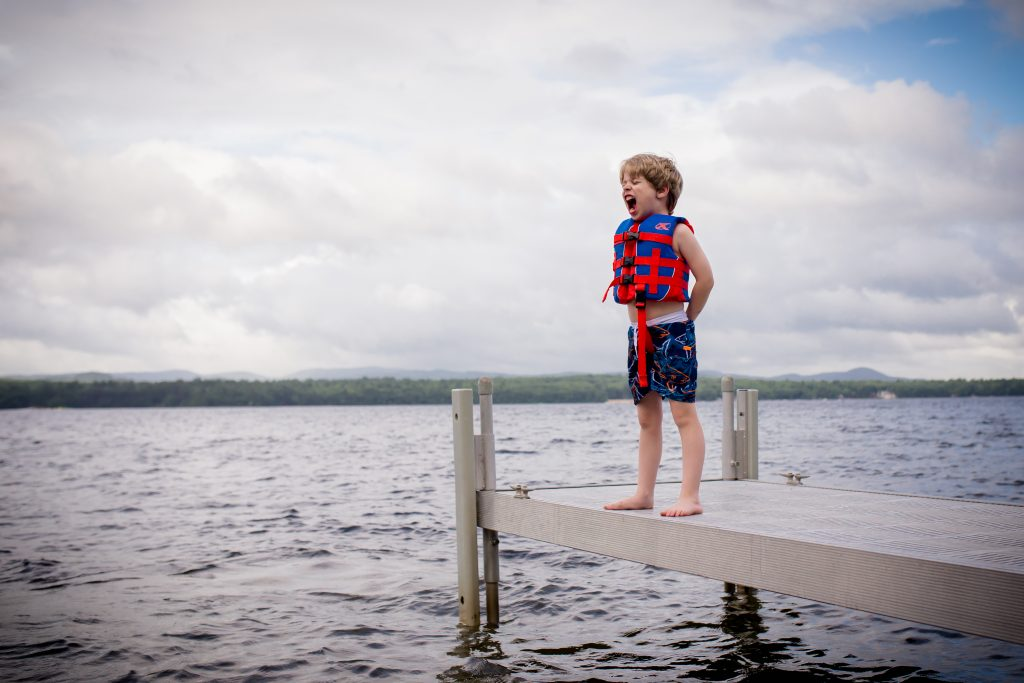 Boy with life jacket screaming on the dock overlooking the water.