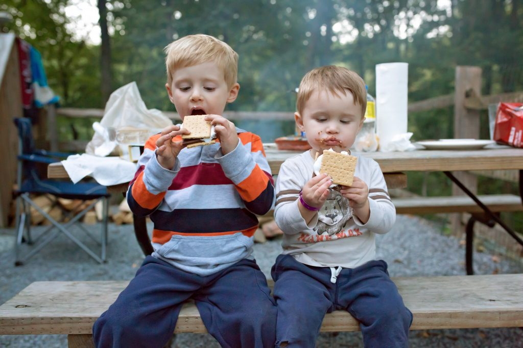 Two young boys eating s'mores at the campsite.