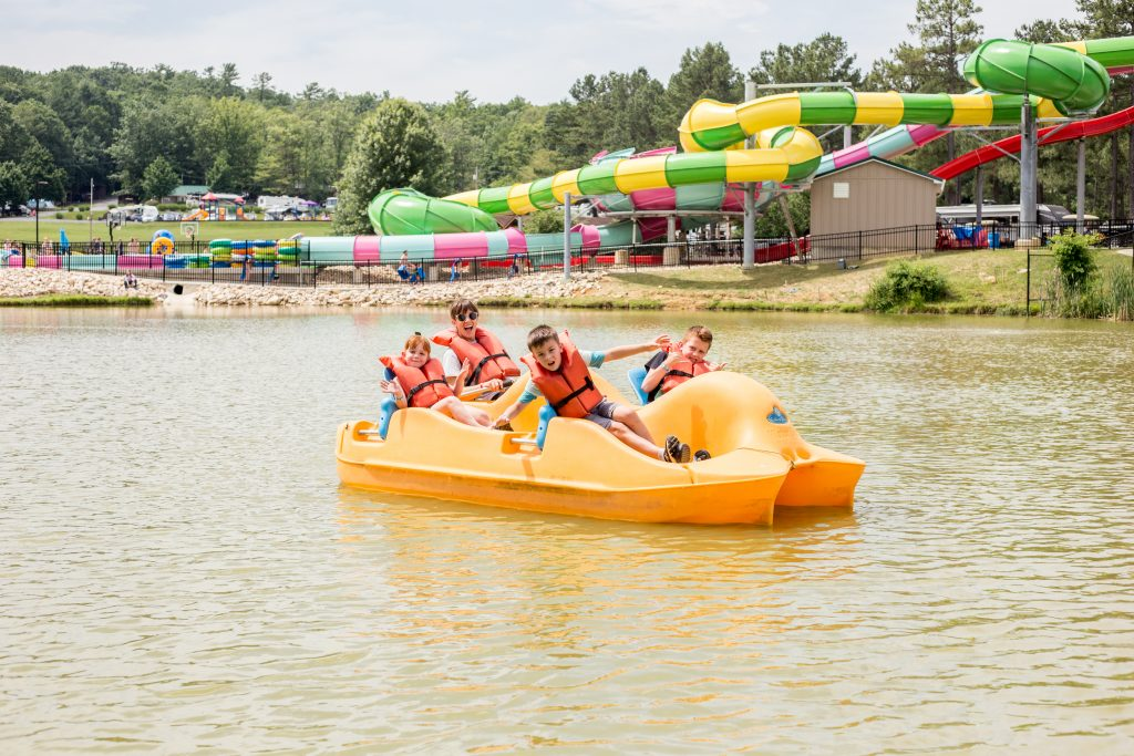 Mother and kids in a pedal boat at a Jellystone Campground.