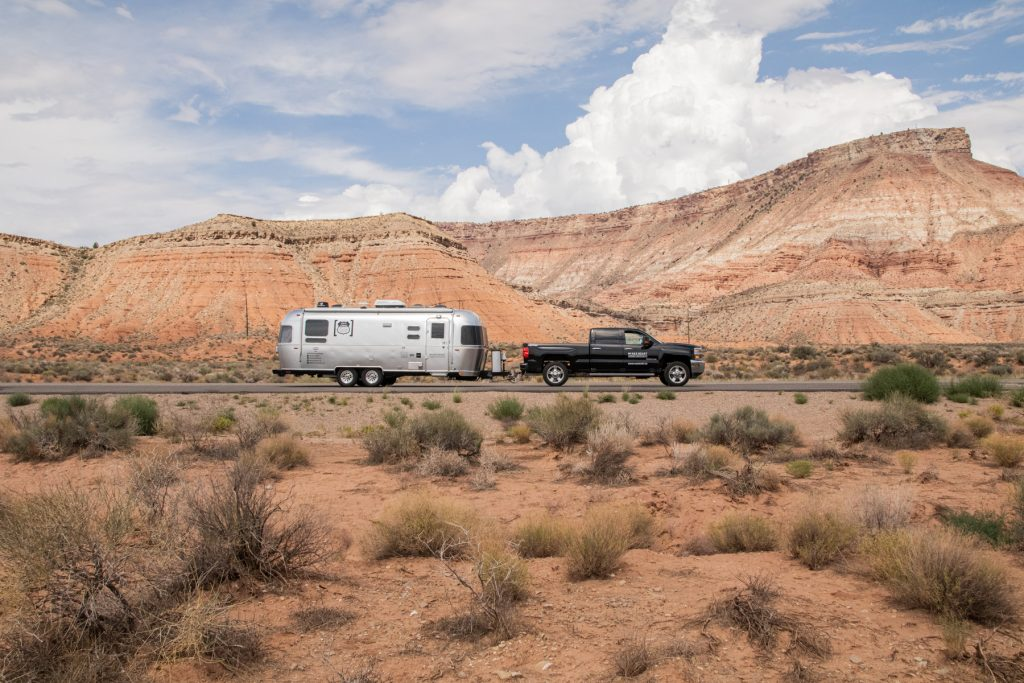 Airstream trailer pulled by Chevy truck surrounded by Utah red rock.