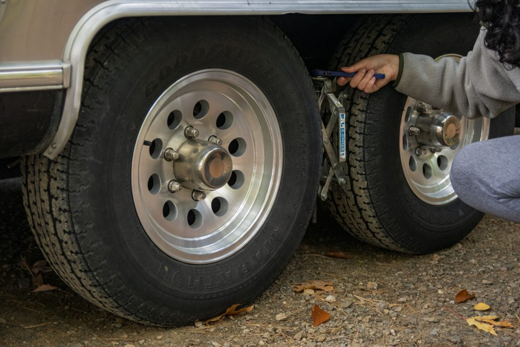 A woman uses a wrench to tighten the tire chocks between the wheels of an RV.