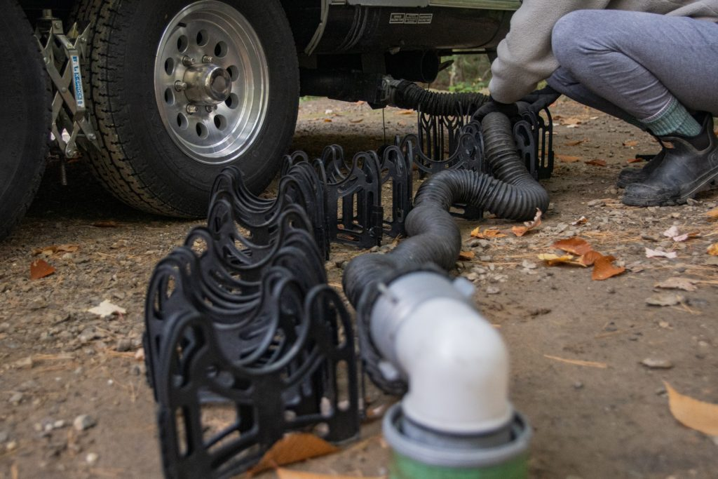 A woman positions her RV sewage hose onto a sewage hose support.