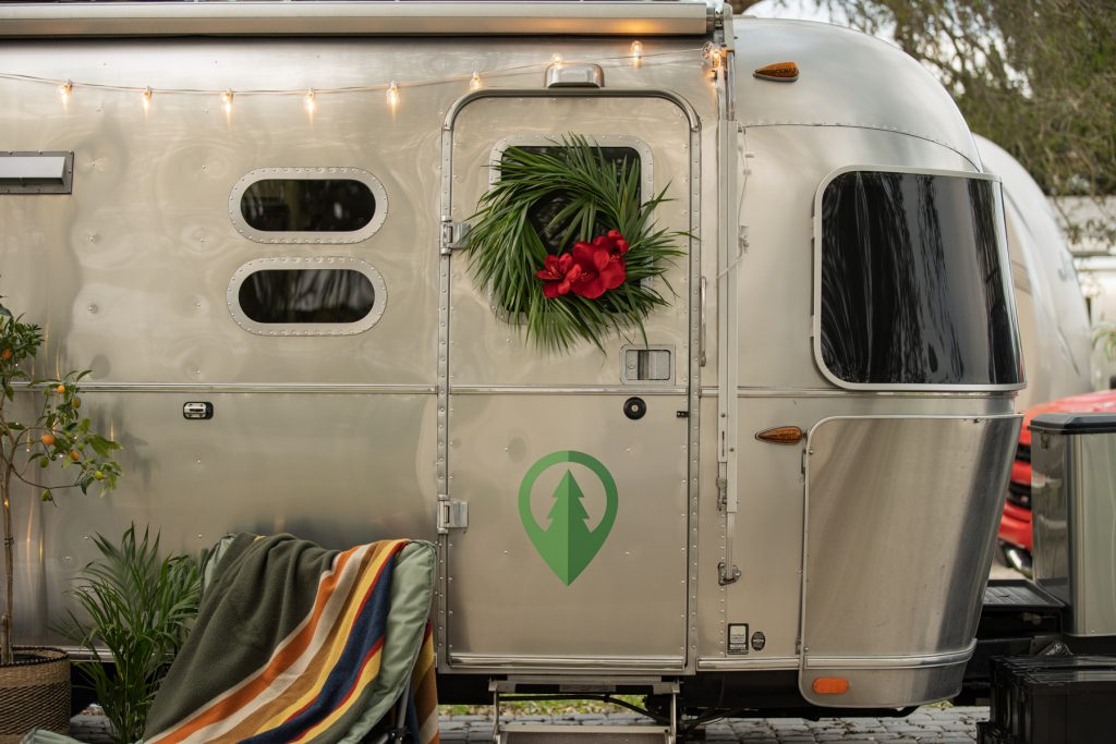 An Airstream trailer with a palm leaf wreath hung on its door.