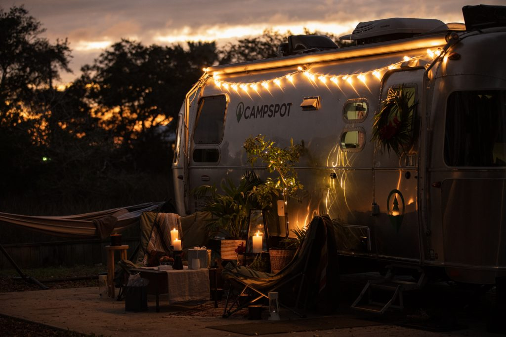 String lights on the outside of an Airstream trailer, decorated for the holidays.