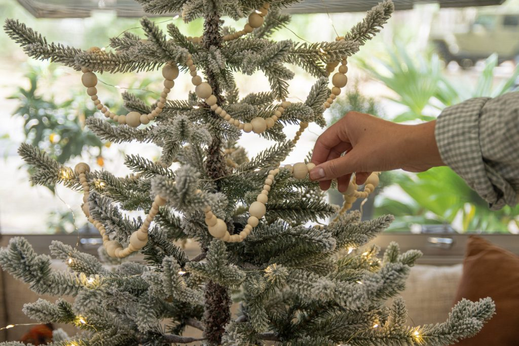 Someone hanging up a decorative white wooden beaded garland around a snowy miniature Christmas tree.