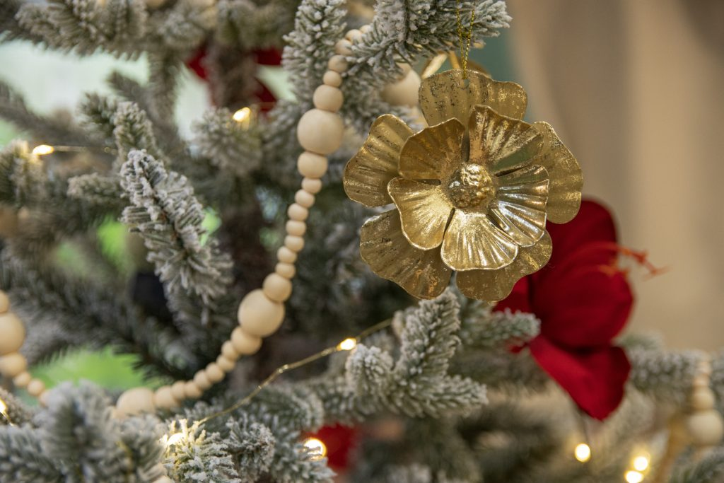 A gold flower ornament hanging on a decorated snowy miniature Christmas tree inside of an RV trailer.