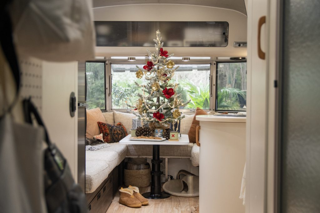 A miniature decorated Christmas tree sitting on top of table inside of an Airstream trailer.