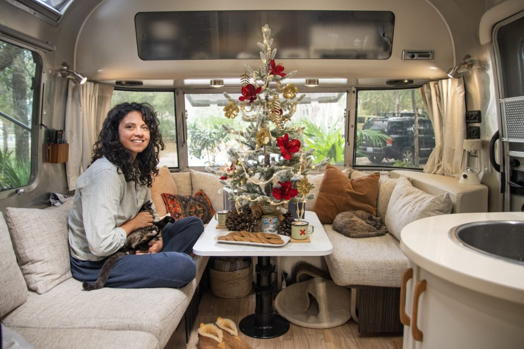 A woman sits on a couch inside of an Airstream trailer, holding a cat. A miniature decorated Christmas tree sits on top of the table surrounded by gifts and treats. A cat sleeps on the other side of the couch.