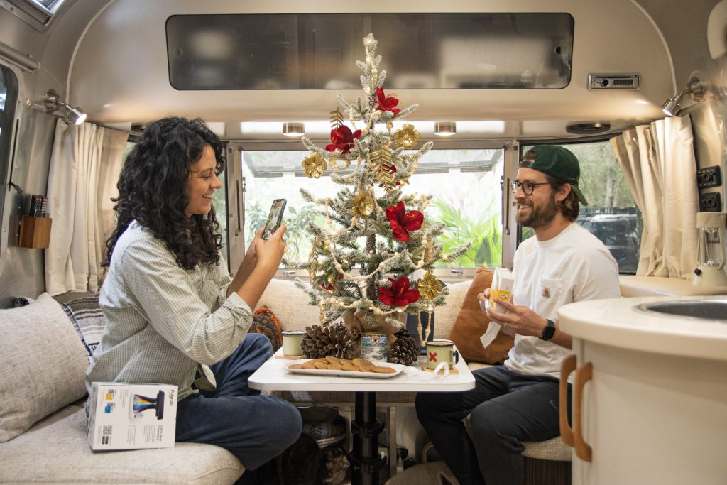 A woman takes a picture of a man holding up his Christmas gift. They are inside an Airstream trailer with a miniature Christmas tree between them.