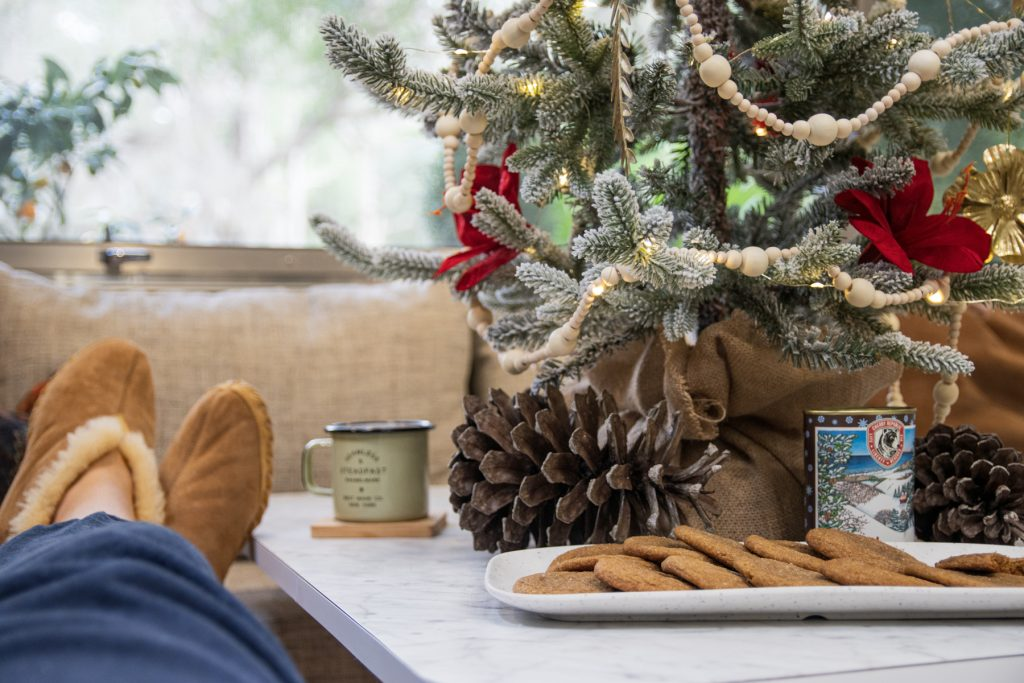 Someone kicks up their feet, wearing comfortable slippers, and is looking at a miniature Christmas tree with cookies and pinecones underneath it. They are inside of an Airstream RV trailer.
